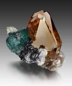 Double terminated, light champagne-colored topaz,  flanked by  green fluorite crystal with strips of albite--the whole on a base made up of a smaller, almost colorless topaz crystal; Topaze Dassu, Braldu Valley, Skardu District, Baltistan, Gilgit-Baltistan, Pakistan