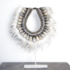 Description: Island luxe vibe. Beautifully hand made from a combination of shells, feathers and nuts. Mounted on a metal stand.Material: Feather, Shell, NutColours Available: OneDimensions:30(w) x 7(d) x 43(h) cm (approximately)