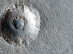 This is a crater on Mars taken by the HiRISE camera. There is so much going on here that is interesting. The light and shadows make it look like it's a mountain rather than a crater, then you have the second crater possibly caused by ice under the surface, lastly the ripple looking things are formed by the martian wind blowing the dust and forming structures like sand dunes on earth.