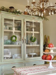 Fruit as Holiday decor wreaths on dish cabinet