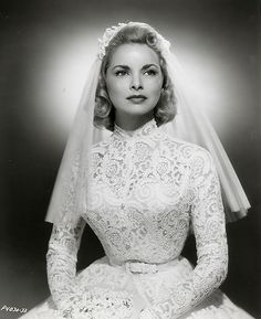 Janet Leigh - lace gown with high neck and fitted bodice & long sleeves.  Tightly cinched waist has narrow belt.  The full skirt flairs out, due to petticoats & crinolines, creating an hourglass silhouette.  Short, above the elbow-length veil completes this 1950's gown.
