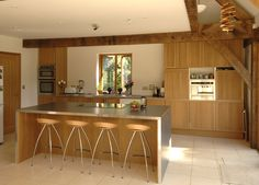 Central kitchen island with electric hob and breakfast bar, tanned oak frame against lighter coloured wooden kitchen cabinets.