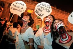 """University students with their necks painted protest at Bolivar square in       Bogota, Colombia, Thursday Nov. 3, 2011. Their signs read in Spanish """"We       have the right to be outraged,"""" left, and """"Excellent education and for all!!""""       Students are protesting education reforms planned by the government that       propose private funding for public institutions. (Fernando Vergara)"""