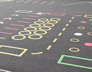 Playground Markings Out on the yard, as the kids run around, the right playground markings can make a huge difference to their development as human beings. The correct markings on a surface can enhance areas of play and stimulate the minds of children, making them question, be inquisitive and combine play with learning.   There are a number of ways you can look at marking a surface, from the outline of a netball or football pitch on a school yard, to traditional board game markings, numbered…