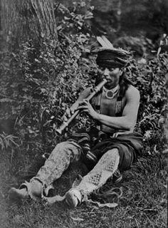 Nikagahi (aka Carey LaFlesche) playing a flute - Omaha/Ponca/Ioway/French/Euro-American - 1911