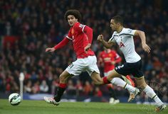 Marouane Fellaini of Manchester United in action with Nabil Bentalab of Tottenham Hotspur during the Barclays Premier League match between Manchester United and Tottenham Hotspur at Old Trafford on March 15, 2015 in Manchester, England.