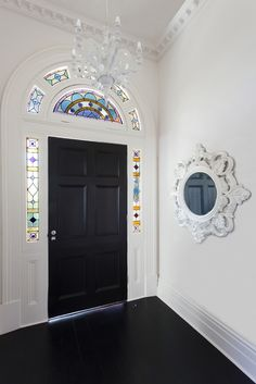 white walls, black floor and door, stained glass accents