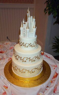Disney castle with golden scrolls on the wedding cake