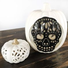 white ceramic pumpkin and a larger white ceramic pumpkin with dawn of the dead skull in the middle
