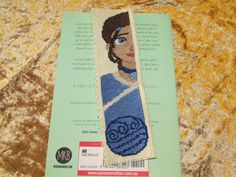 Princess-style profile cross stitch bookmark for Katara of the Southern Water Tribe (Avatar: The Last Airbender). Design at the bottom represents the Water Tribes of both the north and south poles....