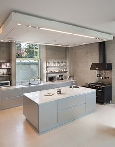 In this kitchen by Elad Gonen and Zeev Beech the bare concrete walls lend an industrial look while the white concrete countertops and floors, open shelves, and no pulls on the cabinetry keep the design extremely minimalist.