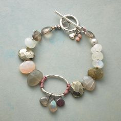 "WHISPERING WINDS BRACELET -- Handcrafted bracelet of labradorite, pyrite, pearl, gray moonstone and pink chalcedony, interrupted midway with a rosy-wrapped sterling oval upon which faceted garnet, labradorite and smoky quartz teardrops dangle. Sterling silver toggle. Exclusive. 7-1/2""L."