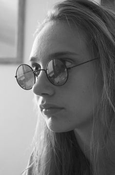 Portrait in black and white of a beautiful girl with round glasses