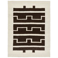 """A wide ivory border frames the simple geometric motifs executed in espresso hues on this wool rug, handwoven in South Africa. From the basic symbol for """"water"""" to the decorative patterns of tribal tents, these exotic markings reflect the words, drawings, and general beliefs of the Ndebele culture and can be found nowhere else in the world.<br/><br/>Woven from Karakul sheep's wool (known for its durable thickness), these one-of-a-kind pieces are created by women artisans of the local Ndebele…"""