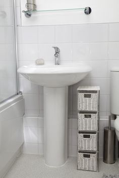 White Pedestal Sink With Nearby Wicker Storage