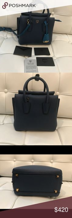 """MCM two tone Mini Milla Leather Satchel! MCM grained leather tote bag with brass hardware. Dustbag included! Used twice No Scuffs,Stains, Rips. Mint condition just like new.  Rolled top handles with hanging logo tag, 3"""" drop. Removable, adjustable strap, 22"""" drop. Hidden magnetic flap closure. Embossed logo at top center. Interior, center zip compartment; slip pocket. Metal feet protect bottom of bag. 6.5""""H x 7.5""""W x 4.3""""D. MCM Bags Satchels"""