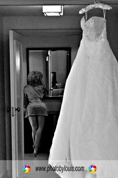 Hanging dress w/bride getting ready in background - Old Hollywood wedding photo. Well done!