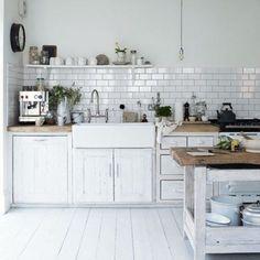 Biała kuchnia z wyspą z drewnianymi meblami
