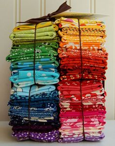 stacked excess fabric scraps to add color and cheerup a bookshelf or desk