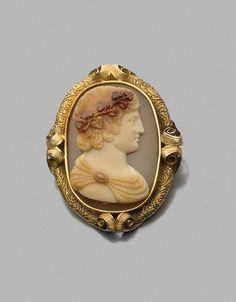Broche ovale dont le pourtour est gravé de rinceaux végétaux et ornée aux quatre côtés d'enroulements de rubans. Elle est sertie en son centre d'un camée gravé d'un buste de Bacchus sous les traits d'Antinoüs.Epoque romantique, vers 1830.
