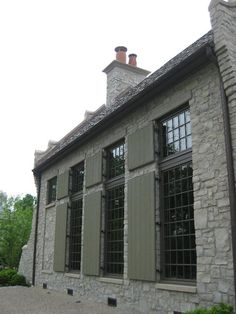 McAlpine Tankersley  love the color of the shutters with the stone...french grey, and black mullioned windows.