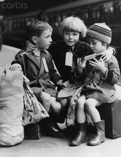 Children wait on the platform at a railway station to be evacuated. 1941.