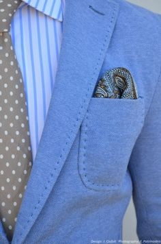 An ideal spring mens look! light blue blazer, dot tan necktie, striped blue shirt, paisley brown pocket square