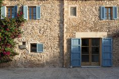 Pops of blue on wooden shutters punctuate the sandstone exterior of a Majorca home