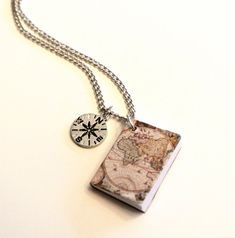Perfect for the world traveler and book lover, this miniature book has an antique style world map for its cover. The book has blank pages for you to write a teeny note or send someone off on a bon voyage! The book is about 7/8 high by 3/4 wide and hangs from a delicate 24 silver tone chain. A mini compass rose charm completes the travel theme. Please remember that the book is made of paper so it will not withstand getting wet.  To view all Trio Artisan Designs necklaces and pendants, please…