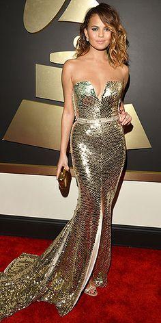 Chrissy Teigen in gold Johanna Johnson gown with deep sweetheart neckline at the Grammy Awards