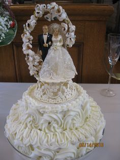 This cute cake is actually a two tier cinnamon roll made by the groom's grandmother. The cake topper is from the bride's grandparent's wedding over 50 years ago.
