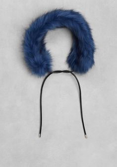 This glamorous faux fur scarf in deep blue adds flair to your wardrobe while keeping you toasty. Featuring leather drawstrings with brass trims that allow to tie the scarf for a neck-warming fit.