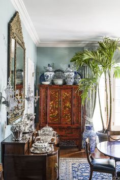 A cabinet is topped with ginger jars, platters, and bowls from Robert Duffy's extensive collection of 18th- to 20th-century blue-and-white ceramics; the curtains are of a Scalamandré damask.