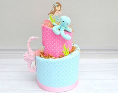 Our Elephant baby cake is classic with a gray and white base and a pop of aqua and pink for a little fun. The new mama will love that this cake is packed with essentials to welcome her little girl. A diaper cake also makes the perfect centerpiece or decoration for an elephant theme baby shower.  We love making it as easy as possible to get your gift to your recipient. If you want us to ship the Baby Cake right to his or her door at no additional charge, simply provide us with a thoughtful…