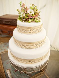 tiered cake with lace accent ribbon topped with sugar flowers