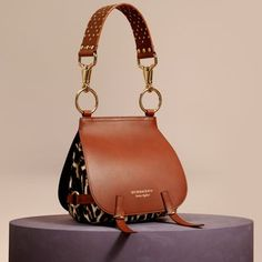 Our equestrian-inspired runway satchel in leopard-print calfskin and smooth bridle leather. Reflecting traditional British saddlery, the soft practical shape is crafted with utilitarian clasps, a grooved border and burnished edges.