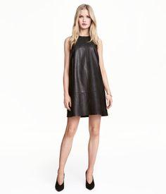 Sort. Lige, ærmeløs kjole i imiteret læder. Kjolen er smalt skåret foroven med bærestykkeskæring. Synlig lynlås bagpå. Med for.