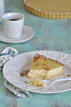 Receta de tarta de leche. Porción de tarta espolvoreada con canela y acompañada…