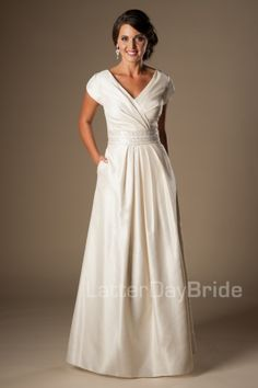 This stunningly cheap modest wedding dress features a flattering ruched bodice cinched by a wide beaded belt and completed by a pleated skirt and rich taffeta fabric. Gown available in Dark Ivory/Silver (as pictured), Ivory/Silver or White/Silver. Older Bride Dresses, Mature Wedding Dresses, Second Wedding Dresses, Western Wedding Dresses, Modest Dresses, 2nd Marriage Wedding Dress, Wedding Dress Older Bride, Wedding Dress Over 40, Isabelle