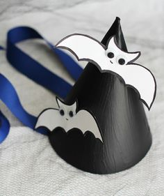 Kids will have fun creating their own party hats to wear during your Halloween soirée. You'll need black acrylic paint, white cardstock, a permanent black marker, googly eyes, glue, and ribbon. Cut out the white cardstock bats beforehand, so the kids can just decorate them with eyes.