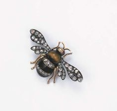 AN ANTIQUE RUSSIAN BEE BROOCH  The tiger's eye and onyx body with diamond line detail to the ruby eyes and rose-cut diamond wings, mounted in silver and gold, circa 1870, 5.4 cm. wide, with St. Petersburg hallmark for gold