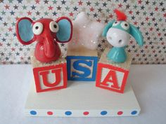 Red White and Blue Republican Elephant and Democrat Donkey sitting on USA wooden blocks