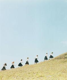 girls walking up a hill... by Osamu Yokonami