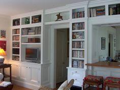 Op maat gemaakte klassieke boekenkast die om de deur heen loopt. Kijk zo'n boekenkast zou ik ook willen hebben in mijn huis. Het doet me denken aan oude huizen met een en suite! En wat zul je daar veel bergruimte in hebben. Ik ben alleen niet zo blij met de goudkleurige knopjes, maar dat is natuurlijk eenvoudig op te lossen :-)