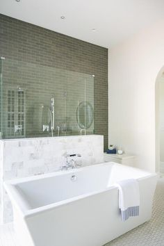 A rectangular freestanding bathtub sits in front of a marble and glass shower accented with gray staggered wall tiles and fitted with two polished nickel shower kits.