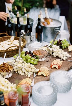 A cheese board featuring an assortment of apples, jams, walnuts, and grapes is a great way to have your guests mingle during a social/cocktail hour. #weddingplanning #reception #cocktailhour #socialgatherings