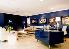 How to use a dark blue on your walls. There is a lot of offset with the light furniture, light floors, and the use of good accent lighting....