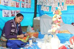 Artisan Pushpa Bhagat from Kolkatta displays the art of making jewellery and decoration items from fish scales at Surajkund International Crafts Mela International Craft, Fish Scales, Stalls, Decorative Items, Artisan, Jewelry Making, Display, Jewellery, Decoration