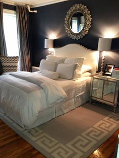 love the contrast of the all white bedding against the moody blue walls and the mirrored accents.