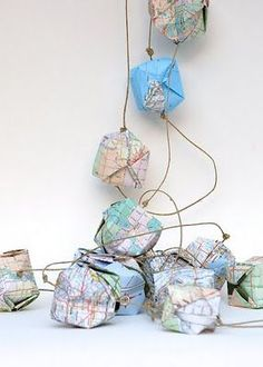 Turning little squares of old map papers into map garland. A good way to put an old out of date atlas to use.